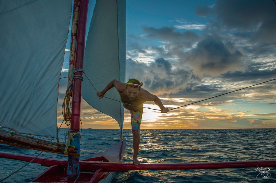 Kite Instructor Alex ifrom FBC Boracay is balancing on the sailing boat after yoga classes